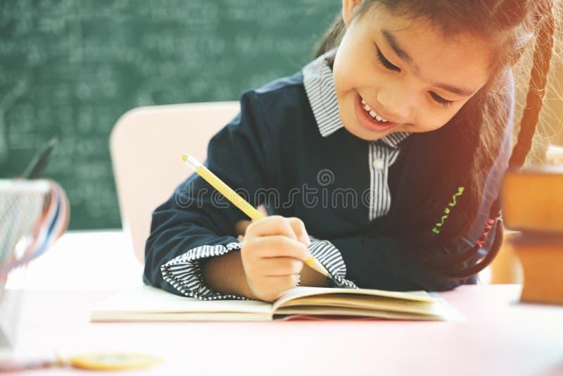 Азиатский студент начальной школы изучая домашнюю работу в классе стоковые фотографии rf
