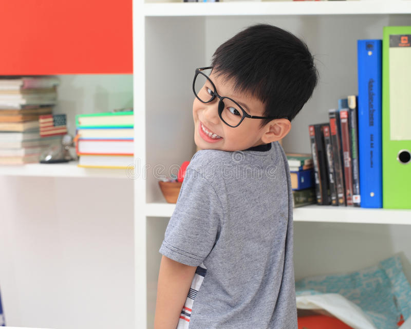Азиатский студент начальной школы смотря камеру усмехаясь пока stu стоковые фото