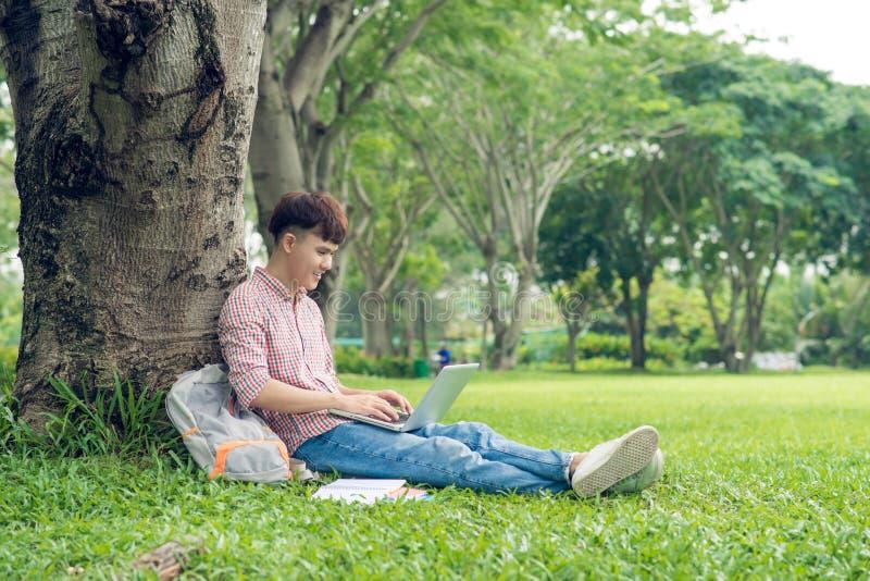 Азиатский студент сидя на зеленой траве и работая на подоле стоковое фото rf