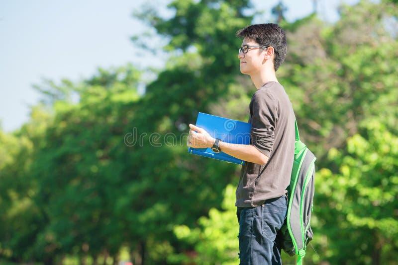 Азиатский студент держа книги и усмехаясь пока стоящ в парке a стоковые изображения rf