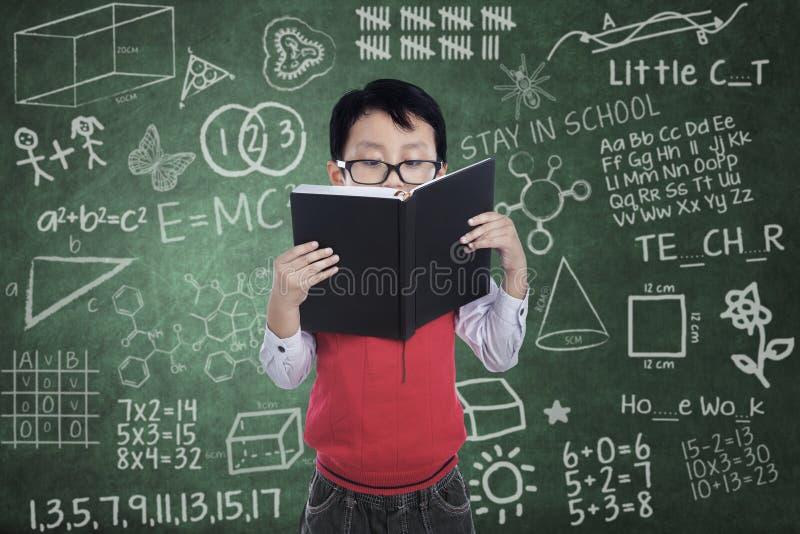 Азиатский студент мальчика прочитал книгу в классе стоковое фото