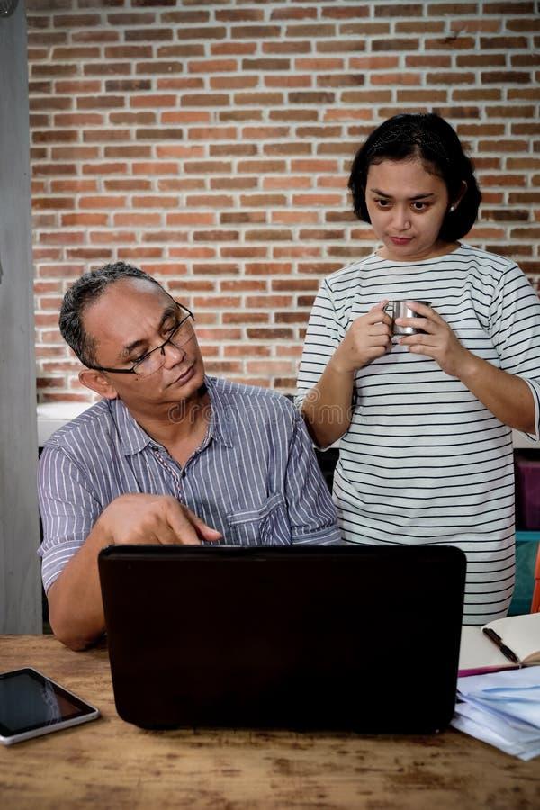 Азиатский супруг и жена имея обсуждение дела дома стоковое фото rf