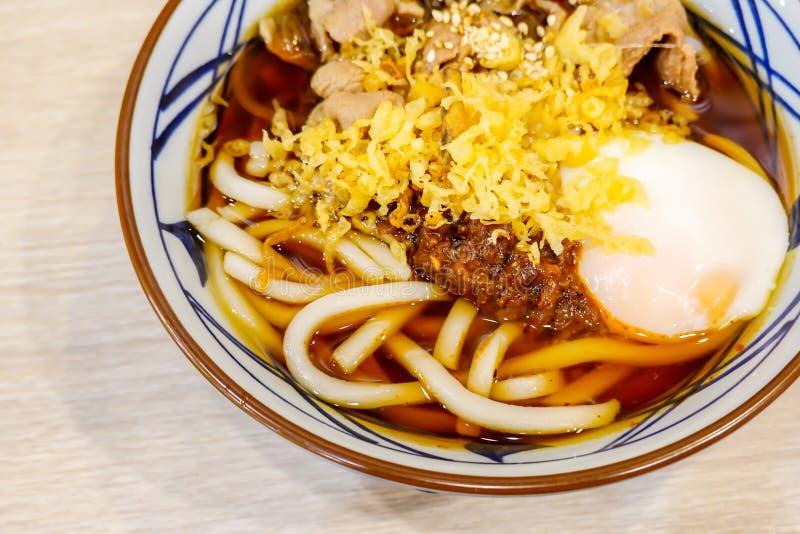 Азиатский суп с японскими лапшами udon, свинина стиля, вареные яйца, бак лапши Udon горячий, конец-вверх в шаре на таблице стоковые изображения rf
