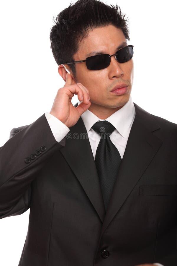 Азиатский телохранитель слушая к инструкциям стоковое фото rf