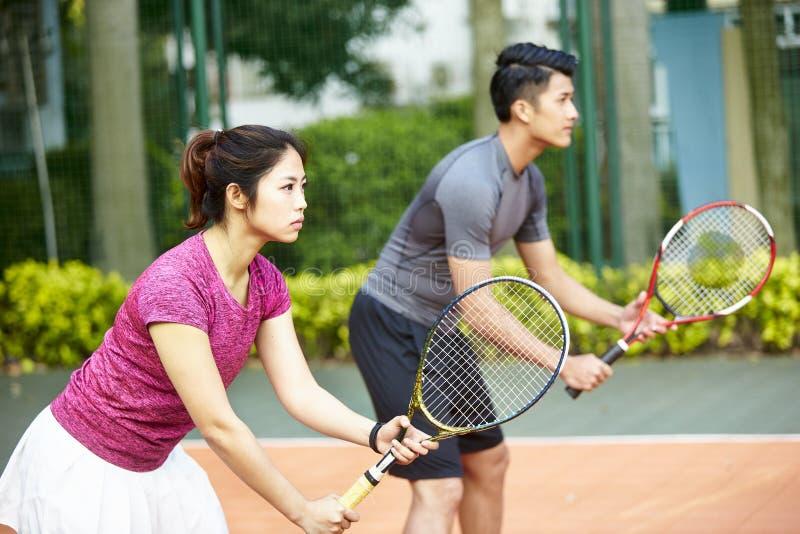 Азиатский теннисист человека и женщины в смешанной двойной спичке стоковое изображение rf