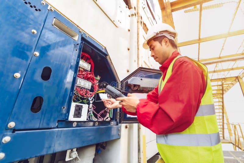 Азиатский техник reefer человека серьезно работающ и контролирующ контейнер reefer на порте Инженер проверяя оборудование стоковое изображение