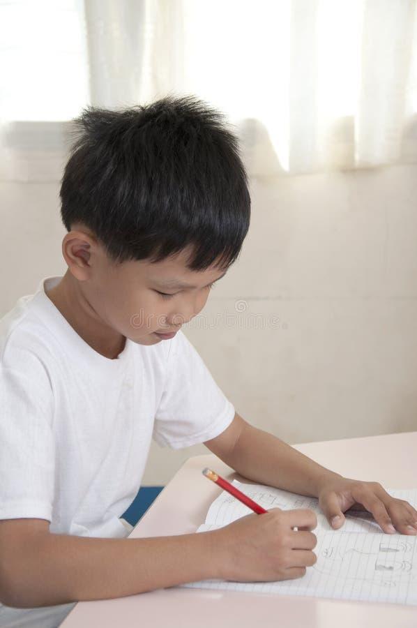 азиатский тип мальчика делает работу домашней комнаты стоковые изображения rf