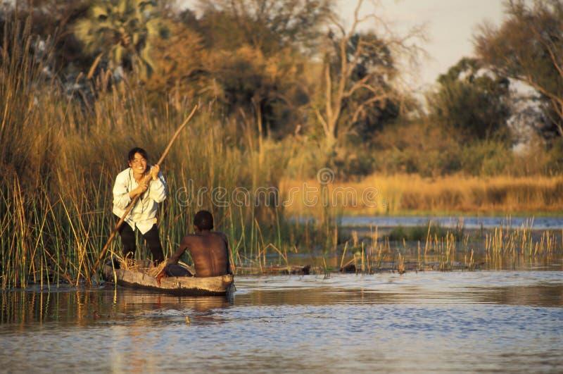 Азиатский турист наслаждаясь отключением на традиционном африканском каноэ стоковое изображение rf