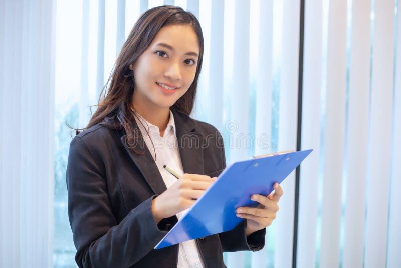 Азиатский усмехаться бизнес-леди счастливый для работы и проверять docu стоковое фото
