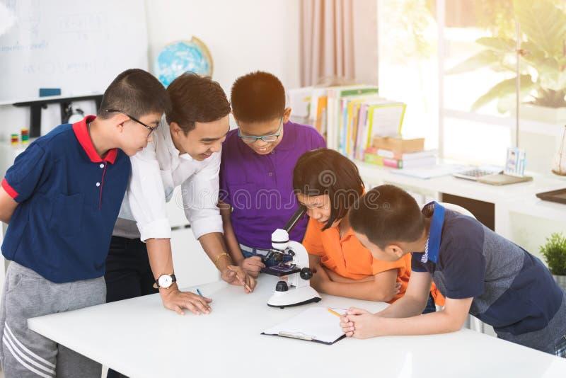 Азиатский учитель расширяя к студенту в уроке биологии с microsc стоковое изображение rf