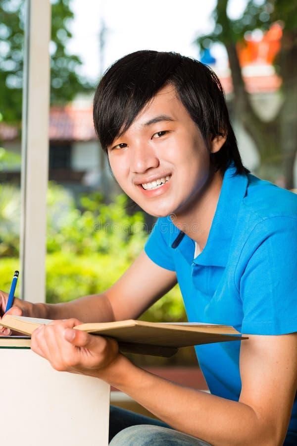 Азиатский учить книги или учебника чтения студента стоковые изображения rf