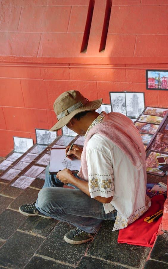 Азиатский художник работая в его студи-магазине искусства улицы стоковое фото rf