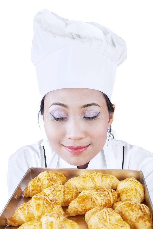 Азиатский хлебопек пахнет изолированным круасантом - стоковые фотографии rf