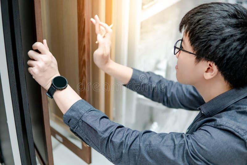 Азиатский человек выбирая материалы шкафа или countertop стоковые изображения rf