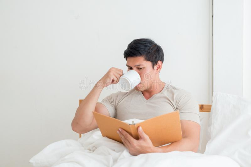 Азиатский человек выпивая чашку кофе или завтрак в кровати стоковые фото