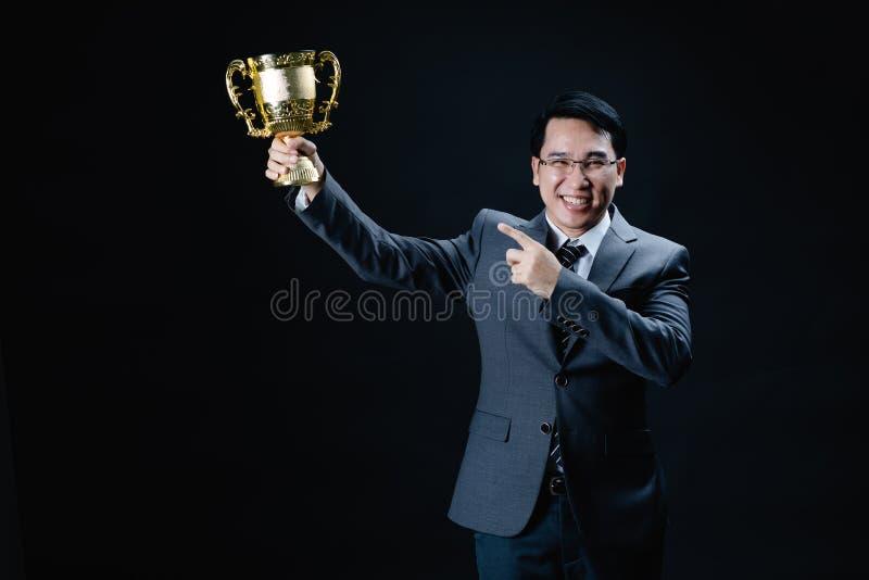 Азиатский человек в официальном трофее удерживания костюма стоковое фото