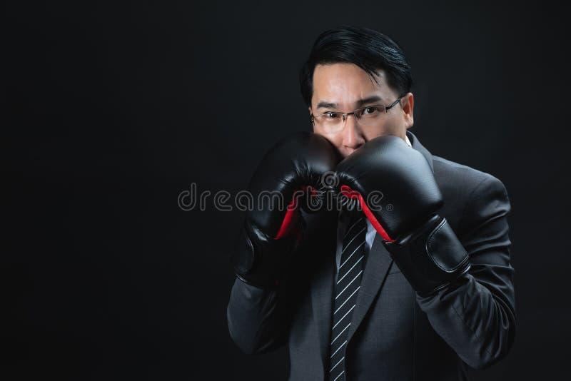 Азиатский человек в официальных перчатках костюма и бокса готовых и уверенном t стоковое фото