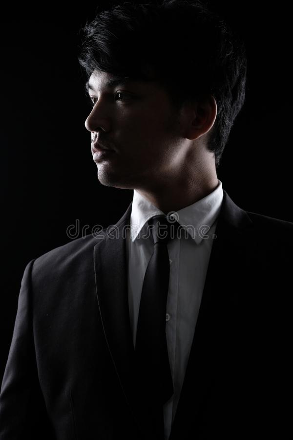 Азиатский человек в черном официально костюме в темноте стоковое фото
