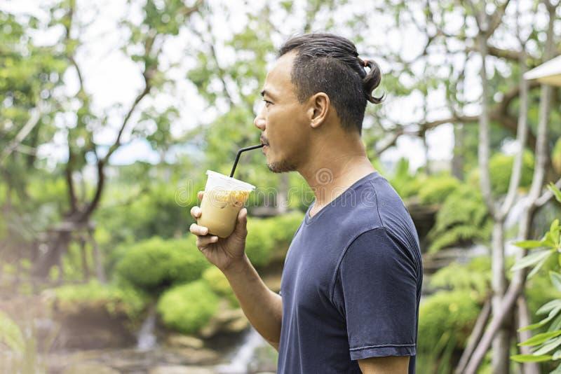 Азиатский человек держа стекло дерева взглядов холодной предпосылки кофе эспрессо расплывчатого стоковые фото