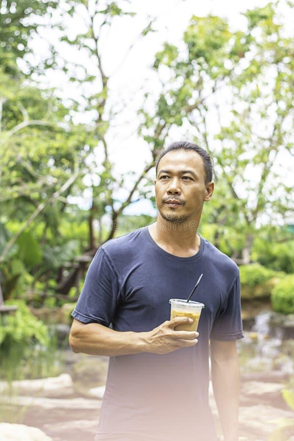 Азиатский человек держа стекло дерева взглядов холодной предпосылки кофе эспрессо расплывчатого стоковое изображение