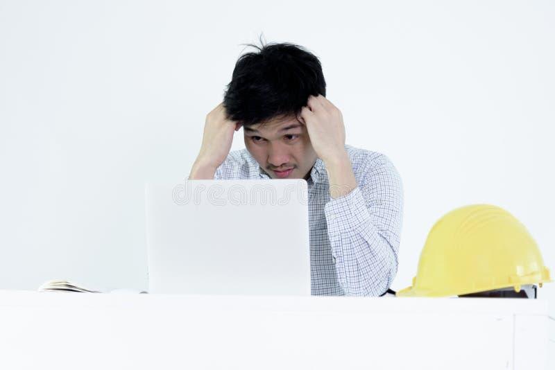 Азиатский человек зарплаты инженера работника сидя на столе и работая w стоковые изображения rf