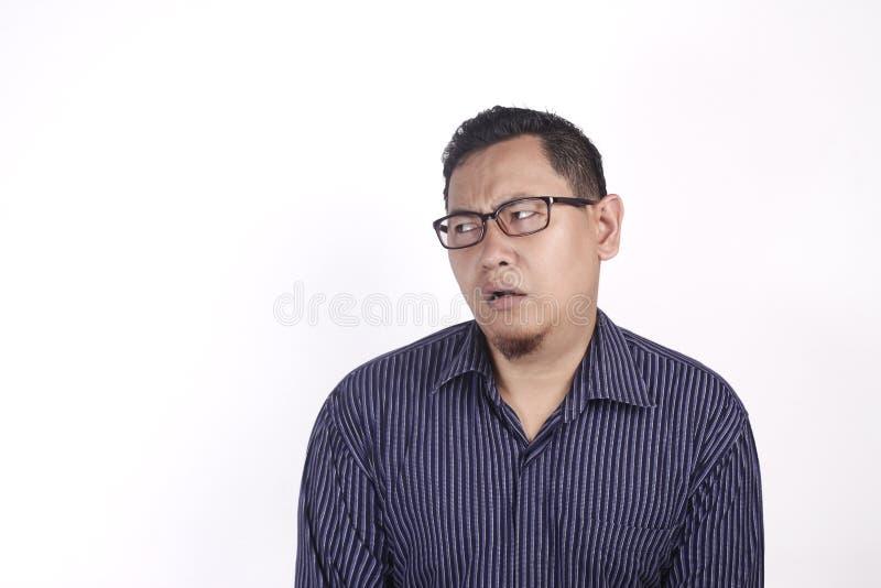 Азиатский человек имея выражение скептичных и неудовлетворенного или недоверия стоковые изображения rf