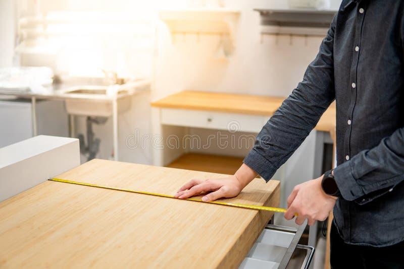 Азиатский человек используя рулетку на countertop стоковое изображение