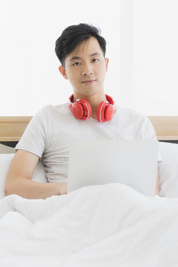 Азиатский человек нося красные наушники, слушая музыку стоковая фотография