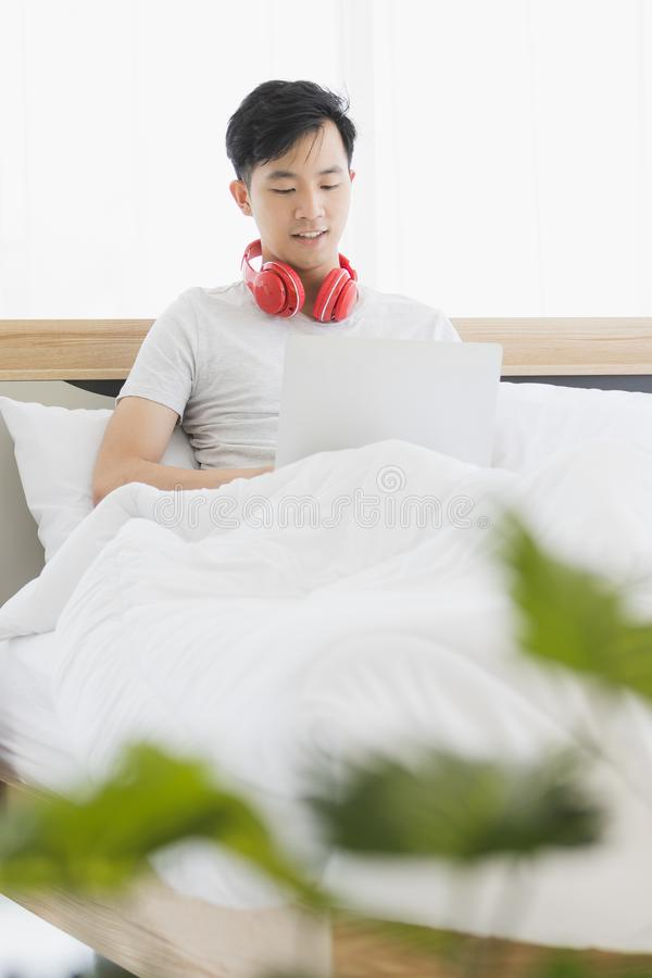 Азиатский человек нося красные наушники, слушая музыку стоковая фотография rf
