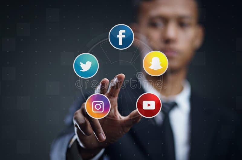 Азиатский человек отжимая виртуальный экран популярных социальных средств массовой информации стоковое фото rf