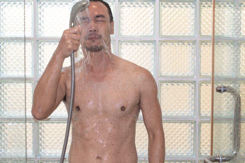 Азиатский человек принимая ливень в ванной комнате стоковое изображение
