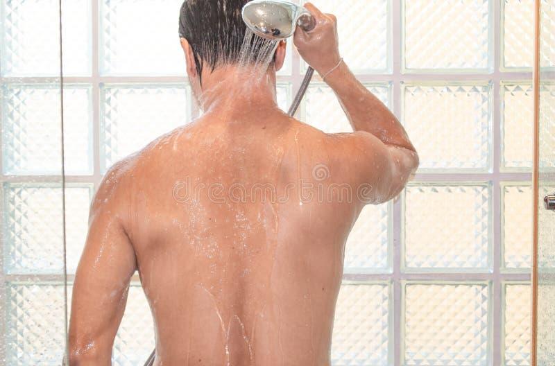 Азиатский человек принимая ливень в ванной комнате стоковые изображения