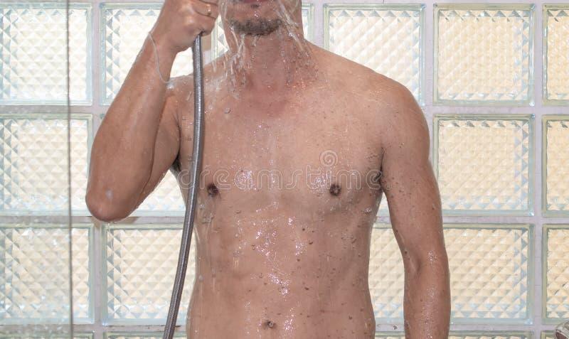 Азиатский человек принимая ливень в ванной комнате стоковые фотографии rf