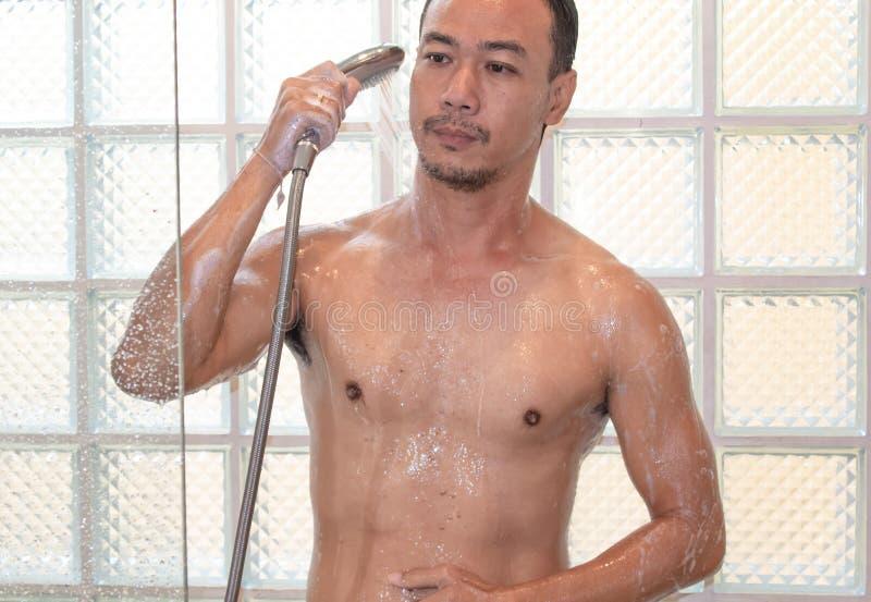 Азиатский человек принимая ливень в ванной комнате стоковое изображение rf