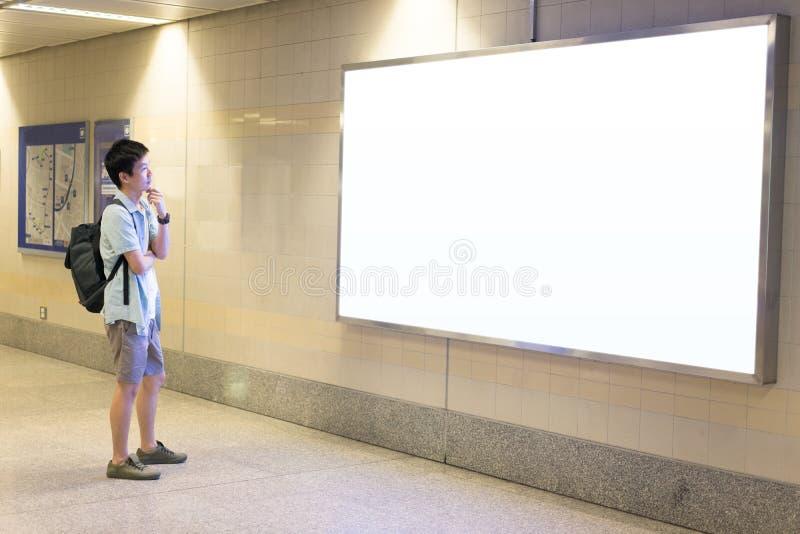 Азиатский человек путешественник выглядя пустой афишей стоковые фотографии rf