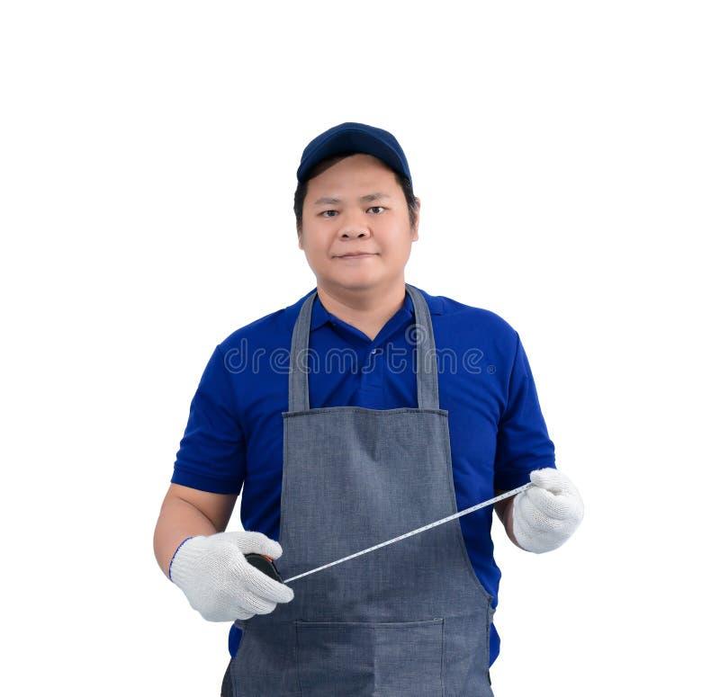 Азиатский человек работника в голубой рубашке с рисбермой и защитные перчатки вручают удержание измеряя ленты изолированный на бе стоковое изображение rf