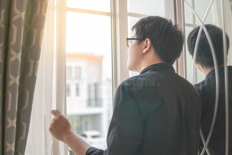 Азиатский человек смотря из окна стоковые фотографии rf