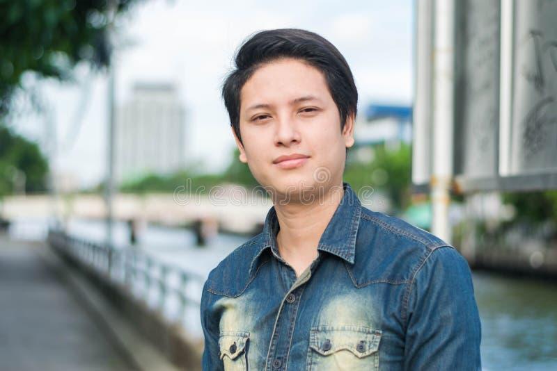 Азиатский человек стоя и показывая его ровная сторона стоковое фото rf