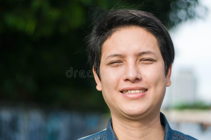 Азиатский человек стоя и показывая его счастливый усмехаться стоковые изображения rf