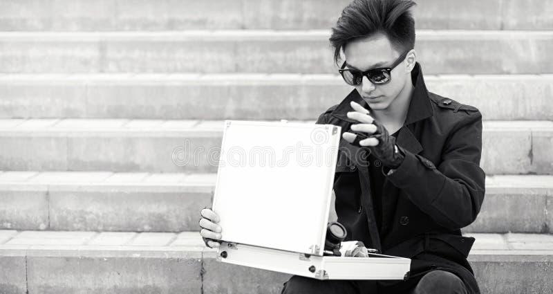 Азиатский человек с чемоданом металла в городе Азиатский и серебряный ca стоковая фотография rf
