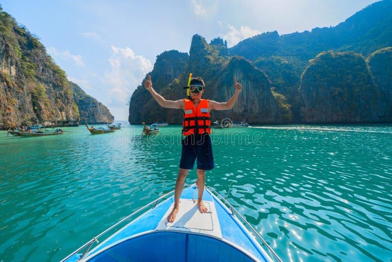 Азиатский человек, турист, стоя на шлюпке к подводному плаванию в Krabi с морем сини бирюзы, море Andaman в Таиланде стоковые фотографии rf
