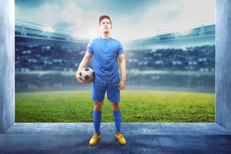Азиатский человек футболиста держа шарик в прихожей стадиона стоковое фото