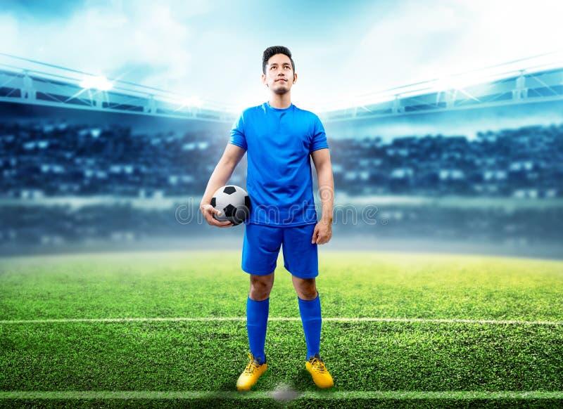 Азиатский человек футболиста держа шарик в середине стоковые изображения