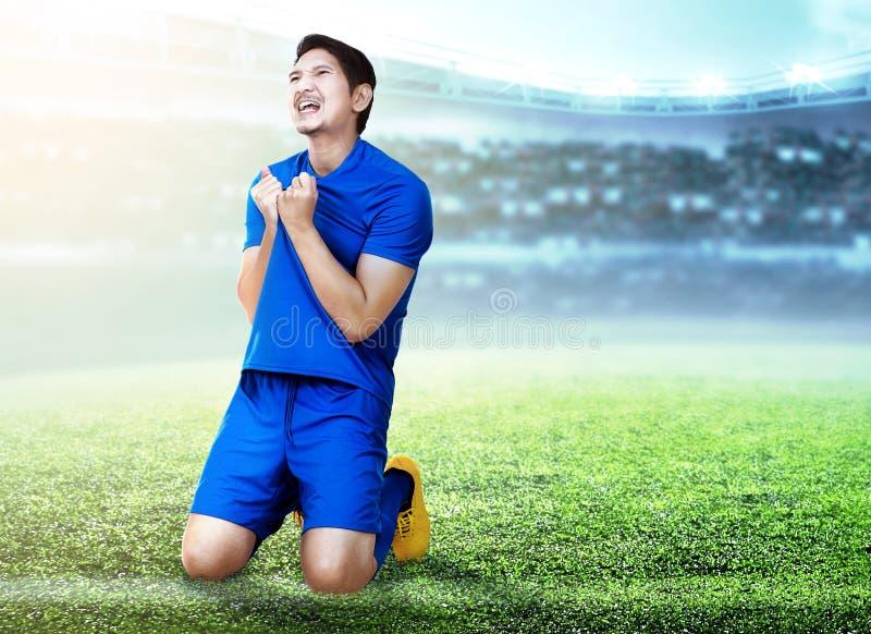 Азиатский человек футболиста празднует цель с удерживанием его jersey и вставать на колени стоковые фото