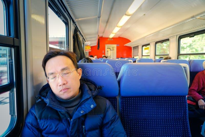 Азиатский человек napping в поезде стоковое изображение rf