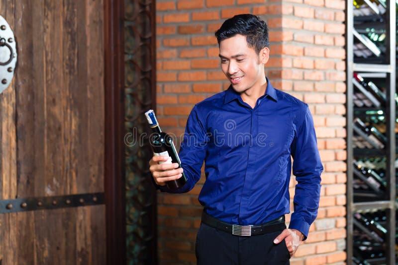 Азиатский человек держа бутылку вина стоковое фото rf