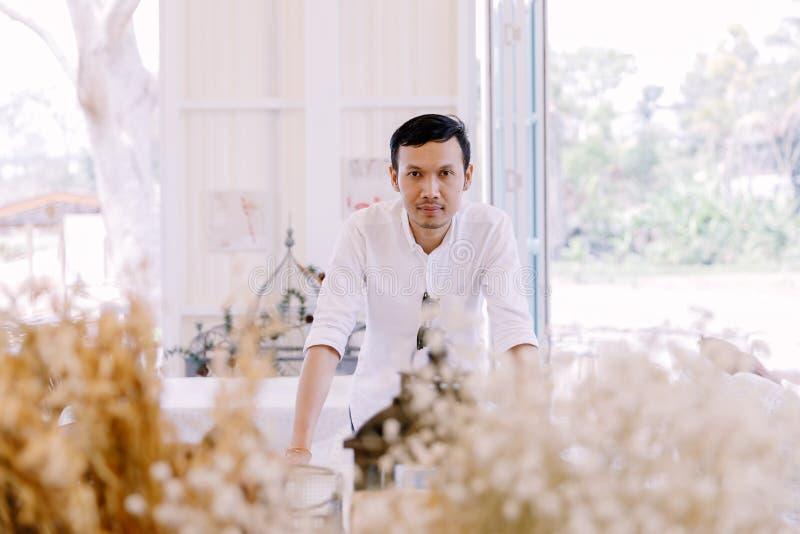 Азиатский человек нося белую рубашку стоя в магазине хлебопекарни стоковые изображения rf