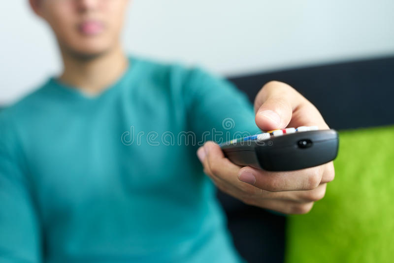 Азиатский человек смотрит канал изменений ТВ держать дистанционное управление стоковые фотографии rf