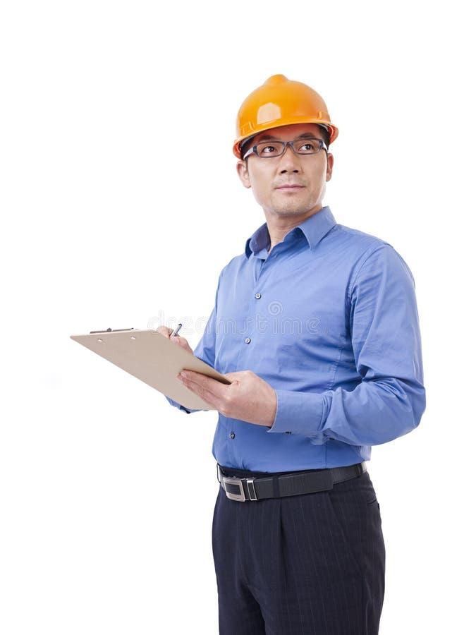 Азиатский человек с оранжевой шляпой безопасности стоковое изображение rf