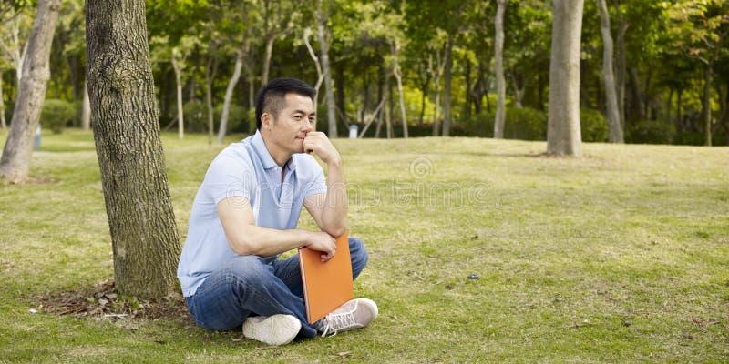 Азиатский человек думая outdoors стоковые изображения